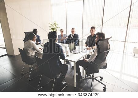 A Team Of Young Businessmen Working And Communicating Together In An Office. Corporate Businessteam