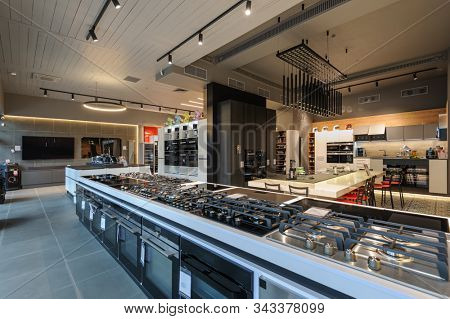 Many gas stoves selling in appliance retail store showroom, ovens and other home appliance at background