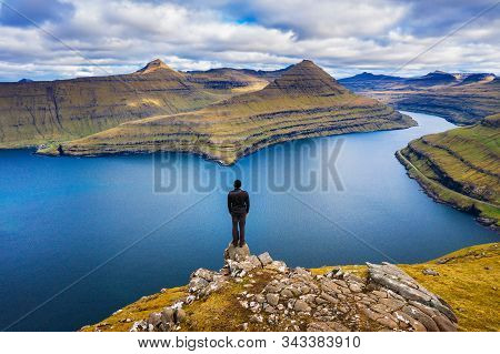 Hiker Enjoys Spectacular Views Over Fjords From The Summit Of A Mountain Near Funningur On Faroe Isl