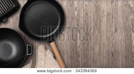 Empty cast iron frying pan on dark culinary background, view from above. Food background with free space for text