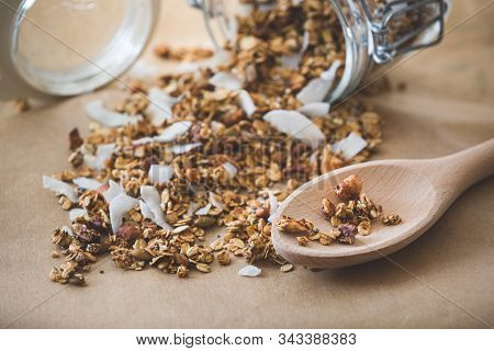 A Wooden Spoon With Granola Next To A Glass Jar On Top Is Filled With Natural Musli With Nuts And Co