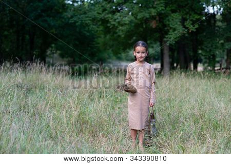 Pretty little girl with long pigtails and beautiful dirty face stands at summer meadow and holding vintage paraffin stove and flask. Orphan, child of war, poverty, hunger, famine, poor destitute kid.  poster