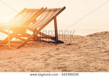 Beach Chair On The Beach With Sunset.