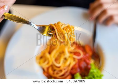 Spaghetti On A Fork. Girl Use Fork With Spaghetti. Pasta With Red Sauce.