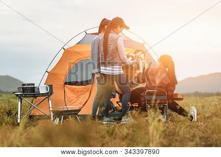 Group Of Friends  Having Fun Together And Drinking At Camping Near The Lake And Mountian Back.