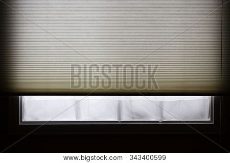 Light by a window in a dark room. Window has net or sheer curtains and a soft paper blind or shade.