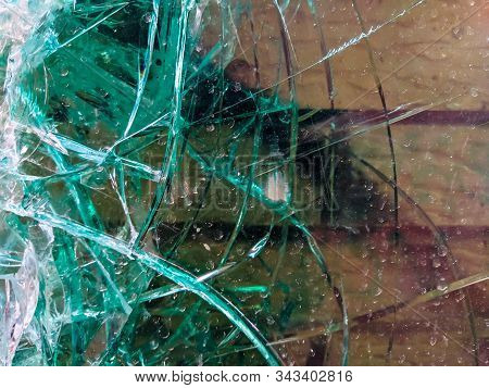 Extremely Damaged And Broken Glass In Green Color During An Accident Or A Fight Where The Window Was