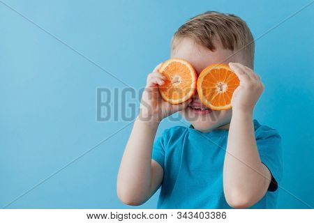 Little Boy Holding An Orange In His Hands On Blue Background, Diet And Exercise For Good Health Conc