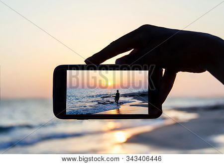 Man Takes A Sunset Photo On The Phone