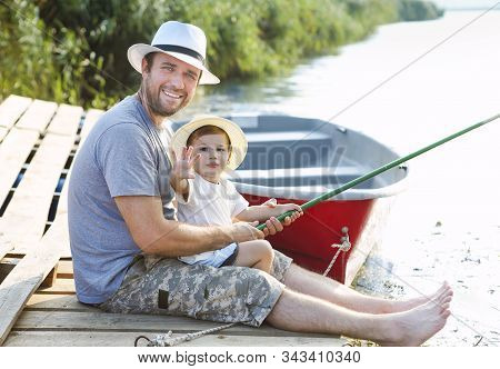Father With Little Baby Son Fishing On The Shore Of The River. Hobby Concept. Angling, Fishing, Acti