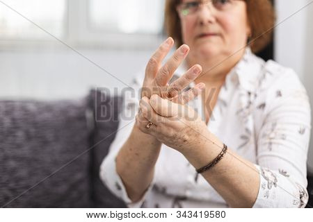Senior Lady Massaging Hand Suffering From Rheumatoid Arthritis. Woman With Osteoarthritis