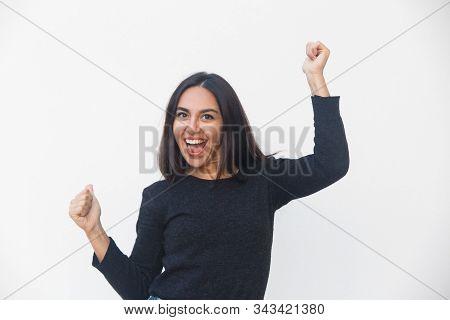 Happy Joyful Woman Dancing And Celebrating Good News. Beautiful Young Woman In Casual Sweater Posing