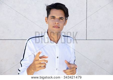 Angry Young Man Pointing To Camera. Emotional Portrait Of Handsome Caucasian Guy Looking At Camera.