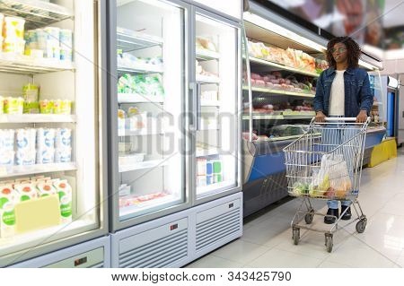 Young Black Woman Walking In Grocery Store, Wheeling Cart, Buying Food. Buyer Shopping In Supermarke