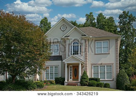 Nice Stucco House With Greren Lawn Against Blue Sky