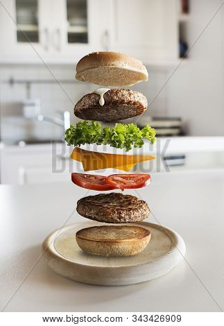Maxi Hamburger With Flying Ingredients Placed In The Kitchen. Conceptual Jumping Burger. Delicious A