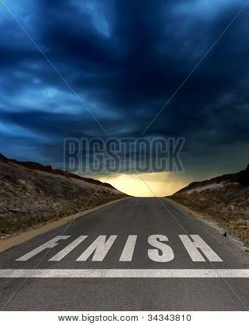 Image of a road with white arrow and finish sign