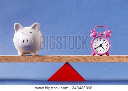 Piggy Bank And Alarm Clock Balanced On Seesaw. Time Is Money Concept