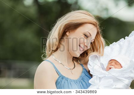 Young Mom With Newborn Baby On Blurred Nature Background.