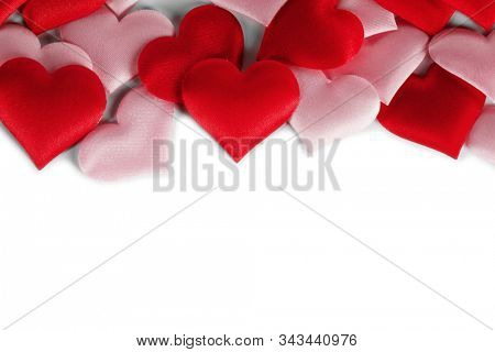 Valentine's day many red and pink silk hearts isolated on white background , border frame with copy space, love concept