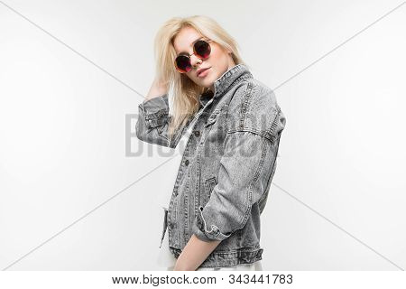 Portrait Of Young Charming Joyful Blonde Girl In Jeans Jacket Possing And Gesticulating In Round Sun