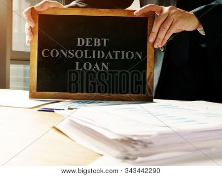 Debt Consolidation Loan Sign And Pile Of Papers.