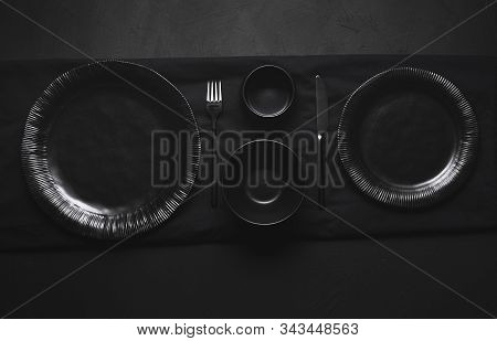 Black Tableware, Plates, Bowls And Cutlery, Empty Dishes, On Black Table. Flat Lay Of Empty Dishes.