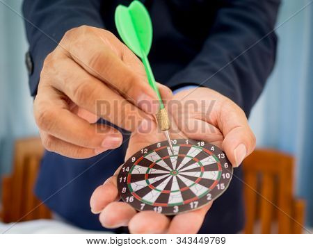 Businessman Holding A Darts Aiming At The Target Center Of Dart Board, Setting Challenging Business