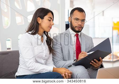 Professional Business Colleagues Discussing Contract. Young Multiethnic Businessman With Folder And