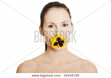 Young naked beautiful woman is standing with the pansy flower in her mouth. Isolated on the white background.