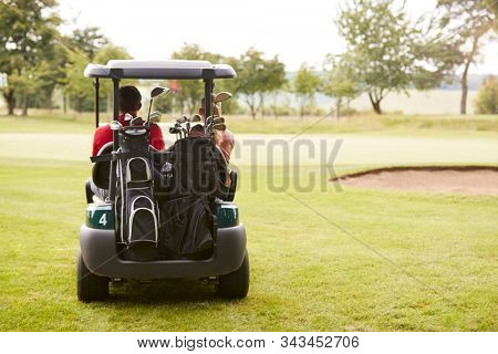 Rear View Of Couple Playing Golf Driving Buggy Along Fairway On Red Letter Day