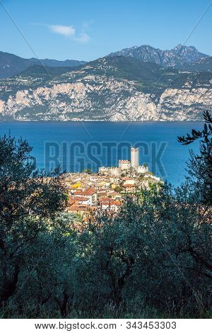 Idyllic Coastline In Italy: Blue Water And A Cute Village At Lago Di Garda, Malcesine, Sunset