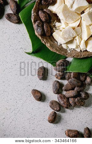 Chopped Pieces Of Raw Organic Cocoa Butter In Craft Ceramic Plate And Cocoa Beans On Green Exotic Mo