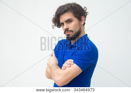 Upset Offended Guy With Folded Arms Looking At Camera. Handsome Bearded Young Man In Blue Casual T-s