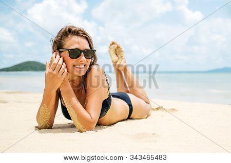 Beautiful Woman With Perfect Body Lying Down On The Beach Sand, Wearing Black Bikini And Sunglasses,