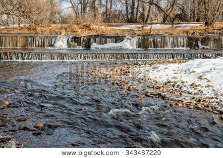 River diversion dam in winter scenery - Cache la Poudre River in Fort Collins in northern Colorado