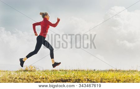 Attractive Young Girl Running Outdoors On Grass. Concept Of Healthy Lifestyle With Space For Text