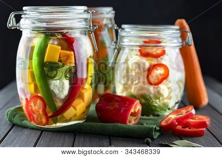 Three Glass Jars Of Fermented Cauliflower, Cucumbers, Carrots, Chili Pepper, Spices, Salt. Vegetable