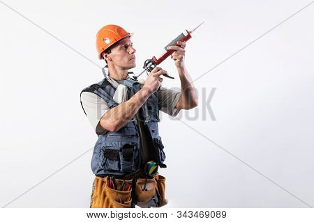 Builder With Sealant. In Work Clothes And Hard Hat. On A Light Gray Background.