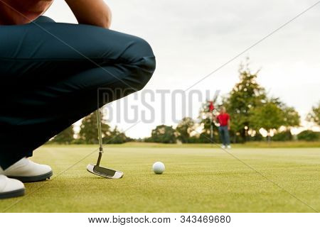 Close Up Of Female Golfer Lining Up Shot On Putting Green As Man Tends Flag