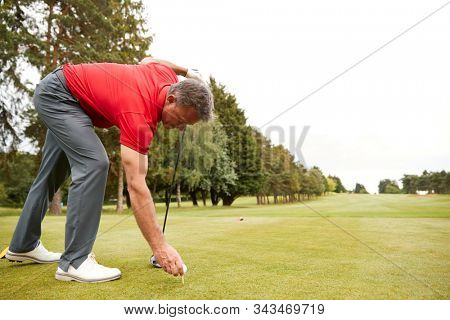 Mature Male Golfer Preparing To Hit Tee Shot Along Fairway With Driver