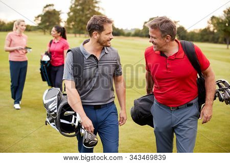 Two Mature Couples Playing Round Of Golf Carrying Golf Bags Along Fairway