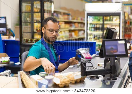 Focused African American Cashier Scanning Goods At Checkout. Concentrated Young Man In Eyeglasses At