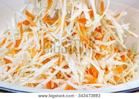 Mix Of Fresh Chopped White Cabbage With Juicy Grated Carrot In The Metal Bowl. Close-up View