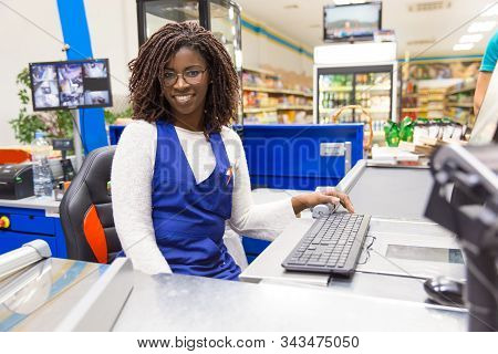 Happy Positive Female Cashier Working In Grocery Store. Young African American Woman Wearing Uniform