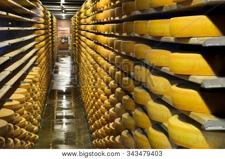 Gruyeres, Switzerland - July 27, 2019: Cheese Wheels Maturing In The Cellar Storage Of The Famous Sw