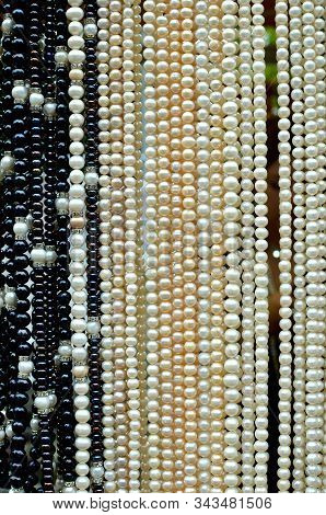 Black And White Shiny  Pearl Beads Background - Perl Necklaces Hanging At The Market, Exhibited For
