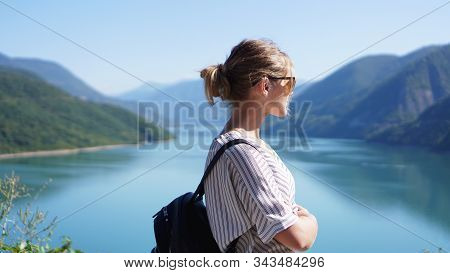 Smiling Woman Against Mountain Landscape And Lake. Zhinvali Reservoir Lake Landscape With Mountains