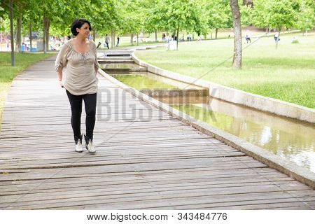 Attractive Middle Aged Woman Walking In Park. Beautiful Brunette Woman Walking On Wooden Pathway And