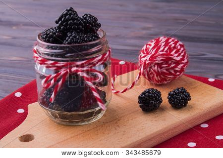 Jar Filled With Blackberries, Colorful Clew. Composition On A Kitchen Board. Red And White Thread Kn